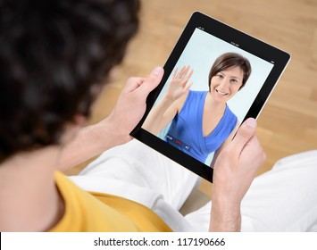 Man and woman communicate through video chat on modern electronic digital tablet.