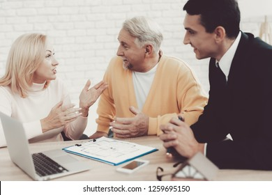 Man and Woman Consulting with Realtor in Office. Important Documents. Real Estate Conceps. Grandfather and Grandmother. People with Gray Hair. Young Realtor in Suit. House for Rent.