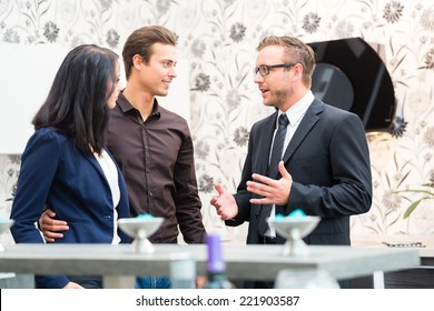 Man and woman consulting salesman for domestic kitchen in studio or furniture store