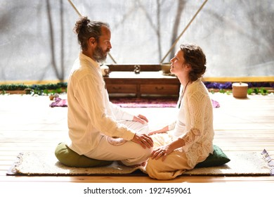 Man and woman couple sitting in lotus posture in tantric yoga practice.