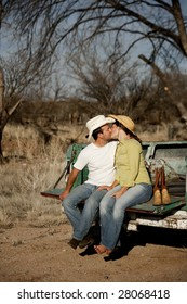 Man and woman in cowboy hats kissing on back of pickup truck