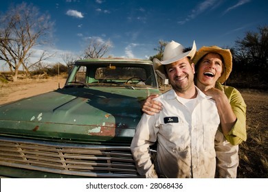 Man and woman in cowboy hats with old truck