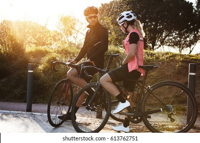Man and woman cyclists spending nice time together, talking, having rest during cycling training in the morning, standing close to each other with road bikes against green trees background in park