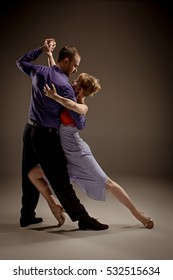 A man and a woman dancing argentinian tango on gray studio background