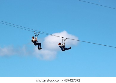 Man and woman descend on a zipline
