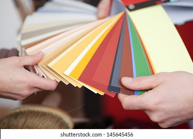 Man and woman discussing new paint colors comparing shades on a set of color cards in a shop