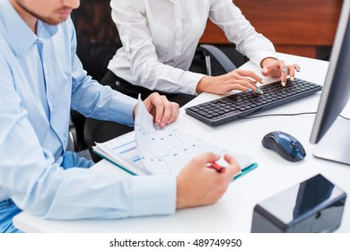 man and woman discussing an office job with graphics  computer