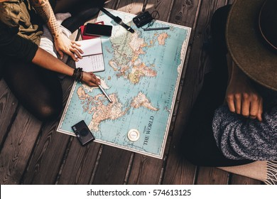 Man and woman discussing tour plans using the world map. Woman making notes and pointing on the map while the man is discussing.
