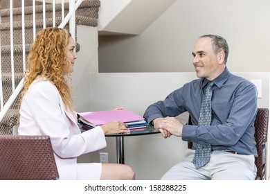 Man and woman discussing work in business office