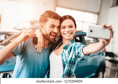 A Man And A Woman Do Selfie Near Their New Car. Automobile Salon. Make A Decision. Happy Together. Great Offer. Happy Together. Successful Buying. Good Mood. Business Trade.