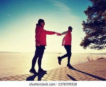 Man and woman do sports at lake against strong morning Sun. Couple enjoy sport together