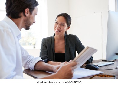 Man and woman with documents in an office, smiling, close up