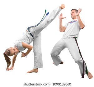Man and woman does the fighting element of capoeira. A couple of fighters train capoeira isolated on white background - concept about people, lifestyle and sport.