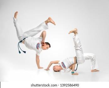 Man and woman does the fighting element of capoeira. A couple of fighters train capoeira on white background - concept about people, lifestyle and sport.
