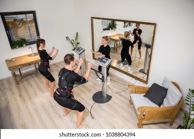 Man and woman doing ems exercising in front of mirror
