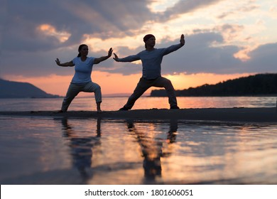 Man and woman doing Tai Chi chuan at sunset on the beach.  solo outdoor activities. Social Distancing. Healthy lifestyle  concept.
