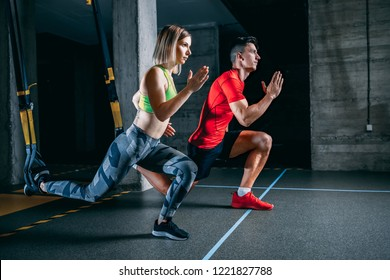 Man and woman doing TRX workout at the gym.