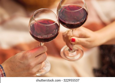 Man and woman drinking red wine. In the picture, close-up hands with glasses. They are celebrating their wedding anniversary.