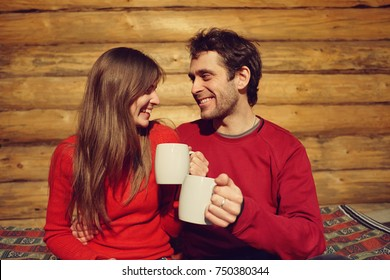 man and woman drinking tea at home. young couple in love with mugs in hands