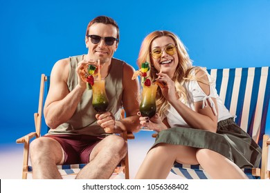Man and woman drinking tropical cocktails resting in deck chairs on blue background