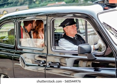 Man and woman driving in vintage taxi and looking through the window