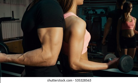 Man and woman with dumbbells in the gym.