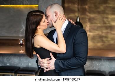 Ein Mann und eine Frau umarmen und küssen sich. Bald Mann in einem Anzug und ein Mädchen in einem schwarzen Kleid mit einer Scheibe in einem Restaurant, Loft. Valentinstag
