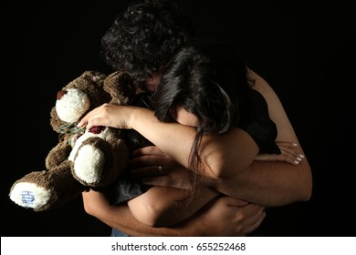 man and woman embracing with a teddy bear