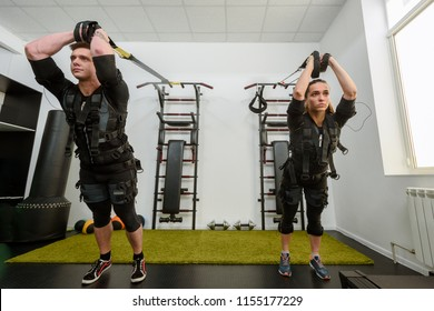 Man and woman in EMS suits doing suspension training