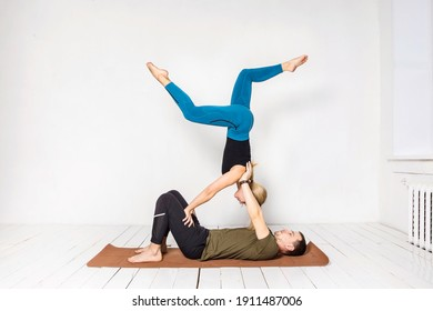 a man and a woman are engaged in acroyoga on a white wooden floor against a white wall