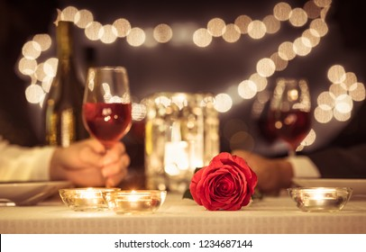 Man and woman enjoying a romantic candle light dinner together.