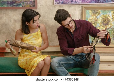 A man and a woman are examining some old masks and things