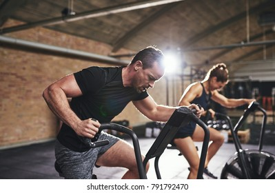 Man and  woman exercising hardly with sport equipment in light gym.