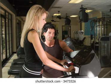 Man and woman exercising together at a fitness center on a treadmill walker exercise machine.  Man could be a personal fitness trainer.