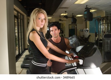 Man and woman exercising together at a fitness center on a treadmill walker exercise machine.  Man could be a personal fitness trainer. Woman is in focus with man slightly out of focus.