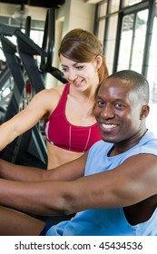 Man & woman exercising together at a fitness center on a stationary bicycle exercise machine.  Woman could be personal trainer. Focus on man in the foreground, woman slightly out of focus.