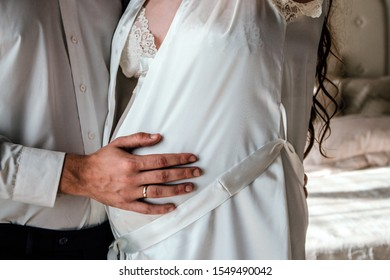 The man and woman are expecting a baby, the husband supports his wife's stomach, they hold hands and full of love, boudoir photo