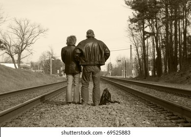 Man and woman facing away, waiting for a train.  Black and white / sepia.