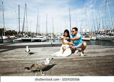 man and woman feeding birds