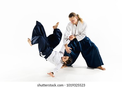 Man and woman fighting at Aikido training in martial arts school. Healthy lifestyle and sports concept. Man with beard in white kimono on white background. Karate woman with concentrated face in