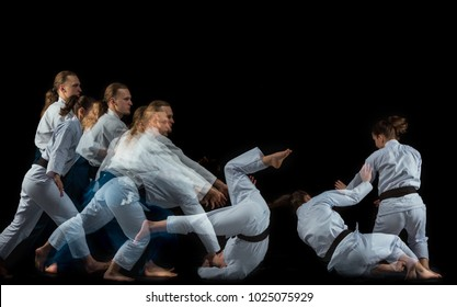 Man and woman fighting at Aikido training in martial arts school. Healthy lifestyle and sports concept. Man with beard in white kimono on black background. Karate woman with concentrated face