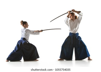 Man and woman fighting at Aikido training in martial arts school with saber. Healthy lifestyle and sports concept. Man with beard in white kimono on white background. Karate woman with concentrated