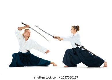 Man and woman fighting at Aikido training in martial arts school with saber. Healthy lifestyle and sports concept. Man with beard in white kimono on white background.
