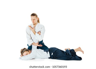 Man and woman fighting at Aikido training in martial arts school. Healthy lifestyle and sports concept. Man with beard in white kimono on white background.