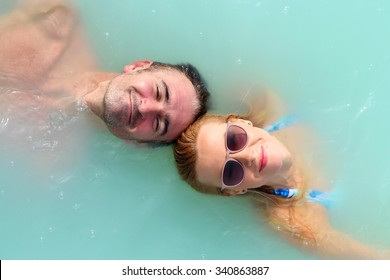 A man and woman float in blue lagoon spa resort in Iceland, their heads are in front each other