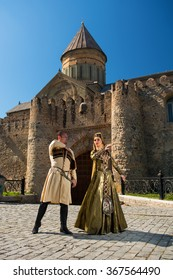 A man and a woman in Georgian national clothes outdoors on a background of an old building