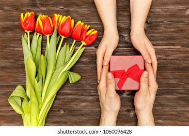 Man and woman gives each other a gift. Red flowers tulips on the dark wood background. Flatlay