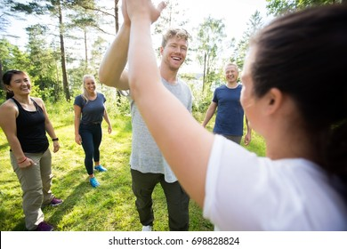Man And Woman Giving High-Five While Friends Standing At Forest