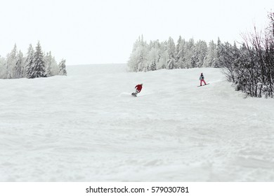 Man and woman go down the hill on the snowboards
