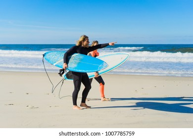 man and woman go to the ocean with surf boards. man and girl go surfing, Portugal, Nazare. Surfing in a wet suit.